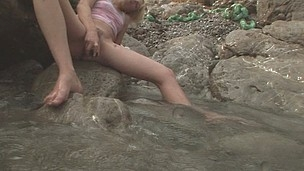 Freaky Alice caressing against a rock to get her pussy wet