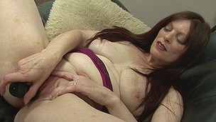Naughty housewife playing with her cookie on the couch